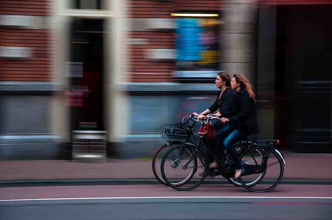 Two women riding bikes on the road