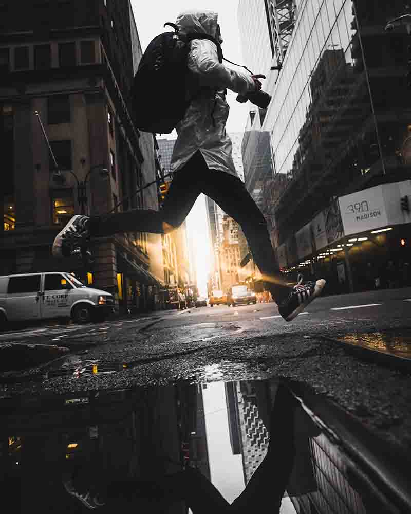 photographer jumping over a puddle of water on the street