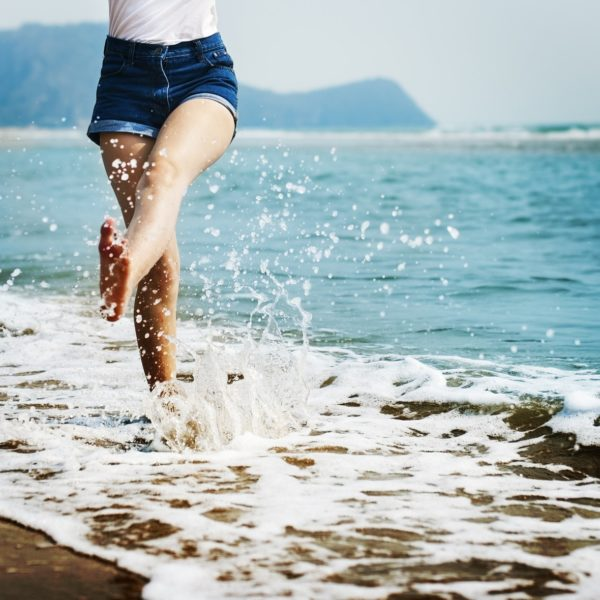 Woman kicking sea water in happiness