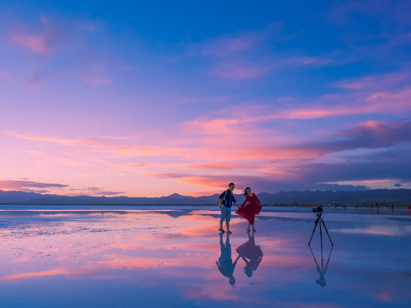 Couple using self timer on the beach during a sunset