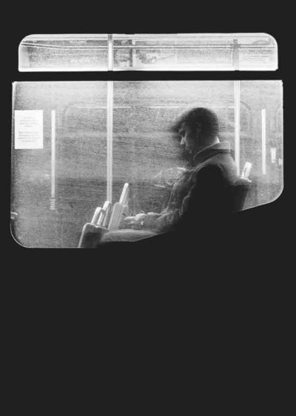 Black and white image of two men sitting in a bus