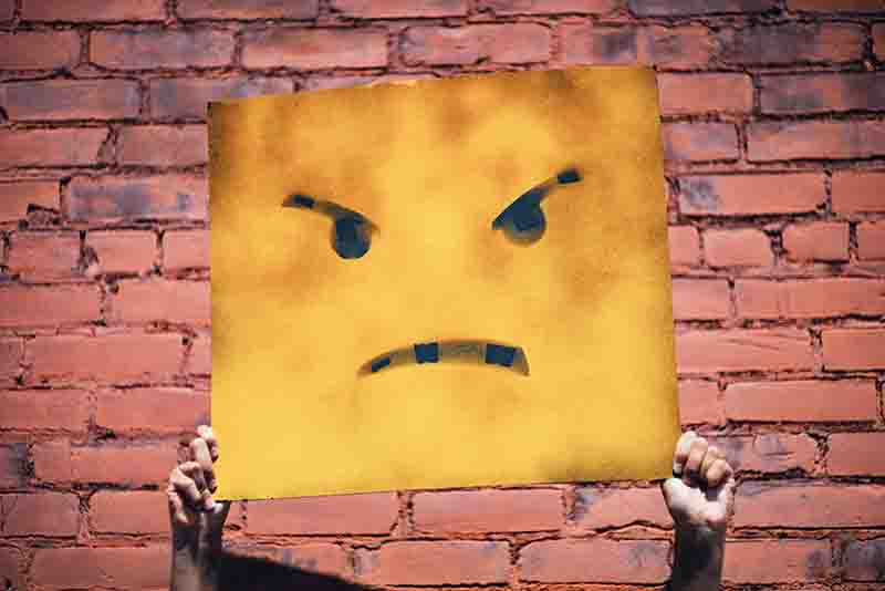 Angry emoticon sign held up by a person in front of a red brick wall.