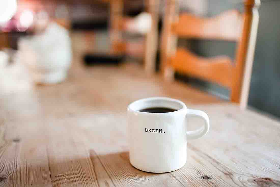 white mug on a tabletop which says begin