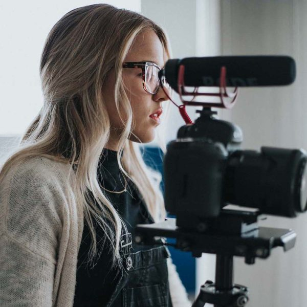 girl photographer with glasses using a DSLR camera with a microphone attached on it