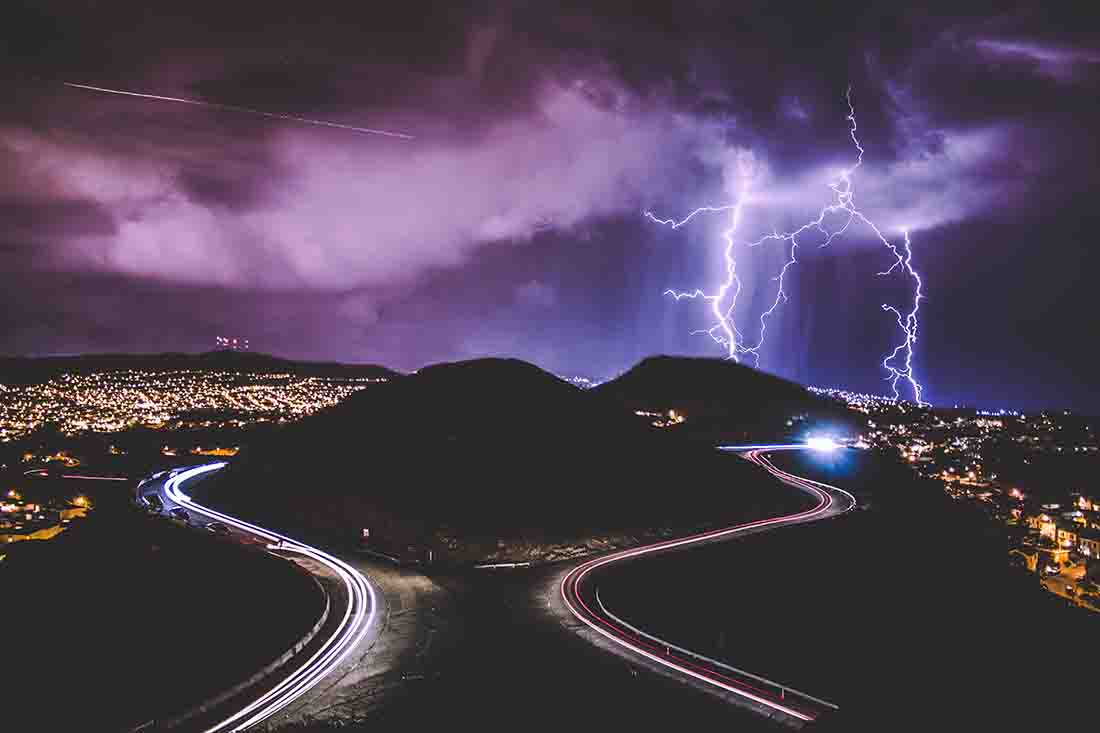 lightning near the mountains with a road winding up all around it