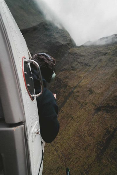 A photographer hanging outside a helicopter for a good photograph