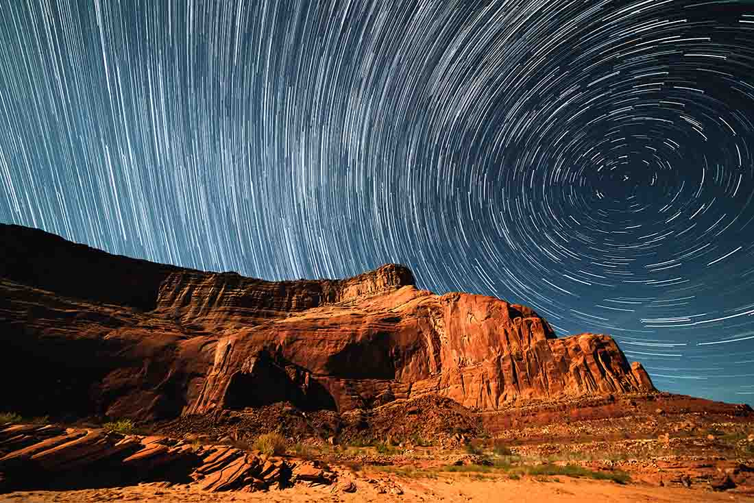 Stunning image of the desert with rocks in the foreground and bright stars circling around in the night sky