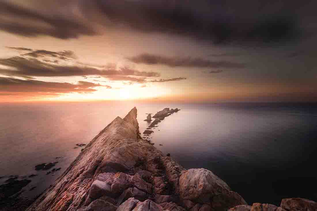 long exposure image of a rock face with the sea below at sunset