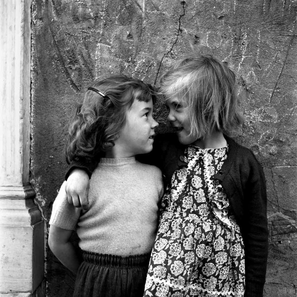 Two young girls looking at each other and smiling