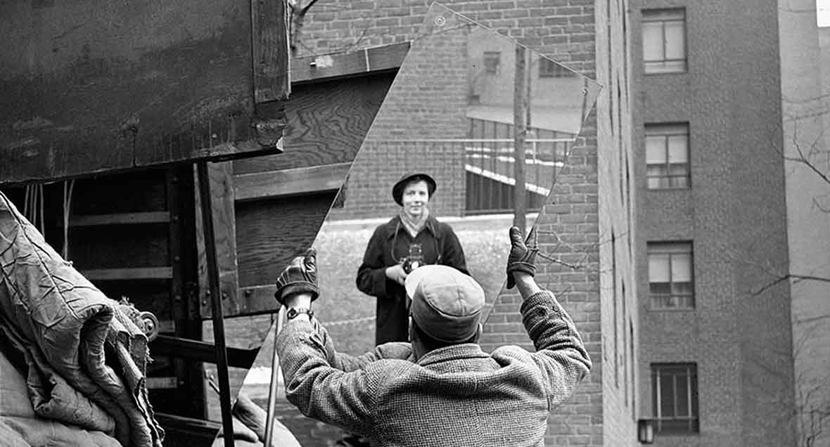 Vivian Maier shooting her own reflection on a mirror carried by a man on the street