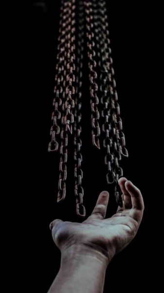a human hand with some chains hanging above it