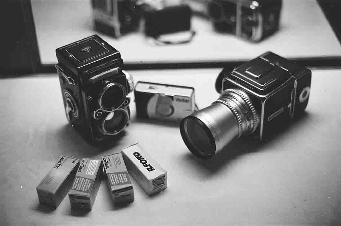 Old cameras with film placed in front of them on a table in black and white