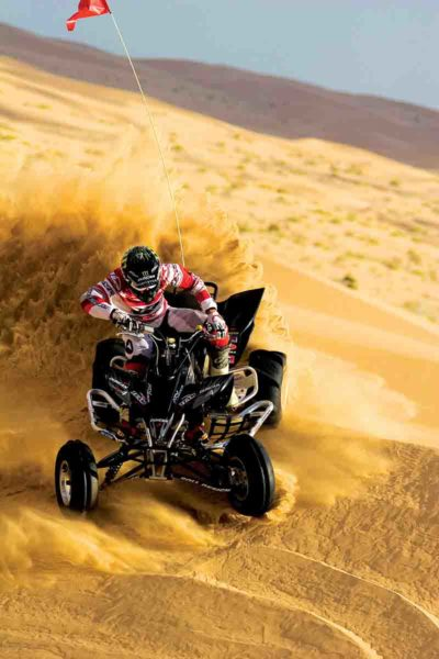 Man on a dune buggy in the sand during the day in s high speed images