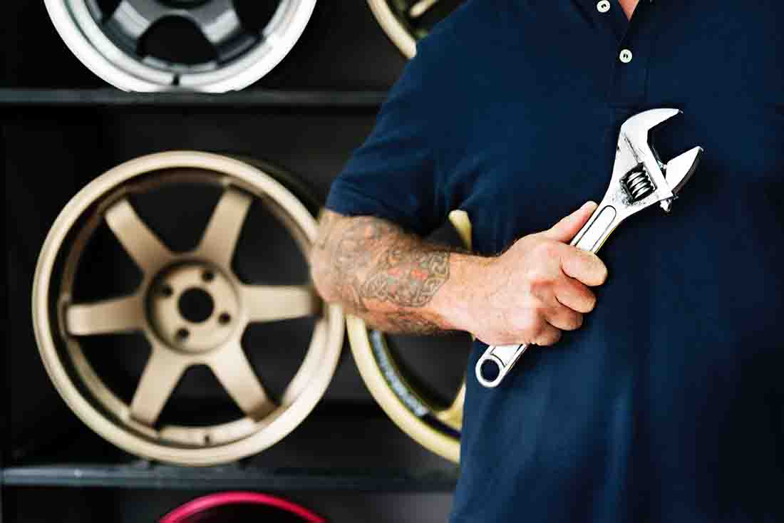 Man holding a wrench in his right hand representing car maintenance