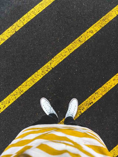 Boy standing on the road with some yellow lines drawn on it
