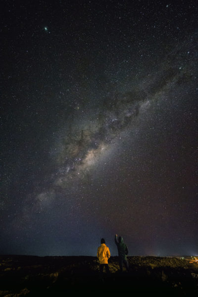 Night image of a landscape with the Milky Way in the background and two men standing on the ground