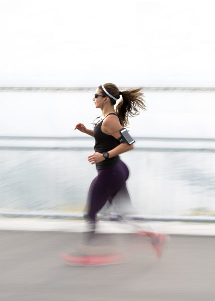 Woman wearing black sports apparel and cellphone attached to her hand running