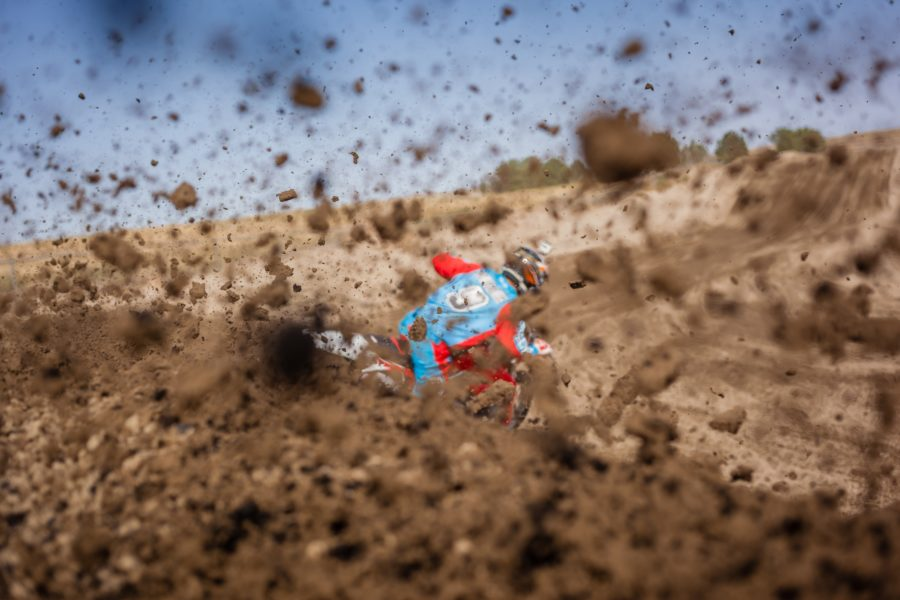 dirt bike running on full throttle with mud flying all round it