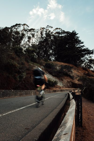 Unsharp blurry image of a cyclist riding through the mountains at dusk. Blurriness caused due to subject motion