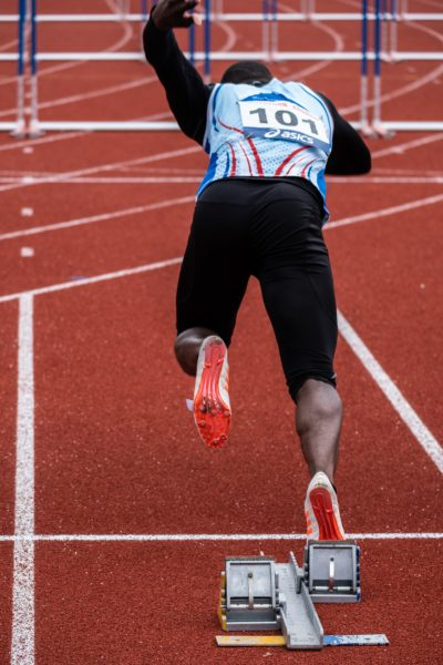 black sprint runner starting a run during a competition