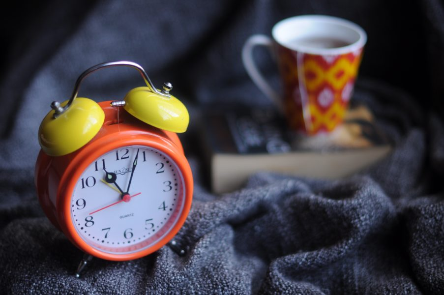 an alarm clock with bells on a towel with a coffee mug in the background