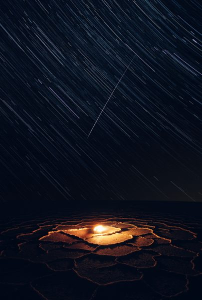 Image of a star trail with a bonfire at the bottom