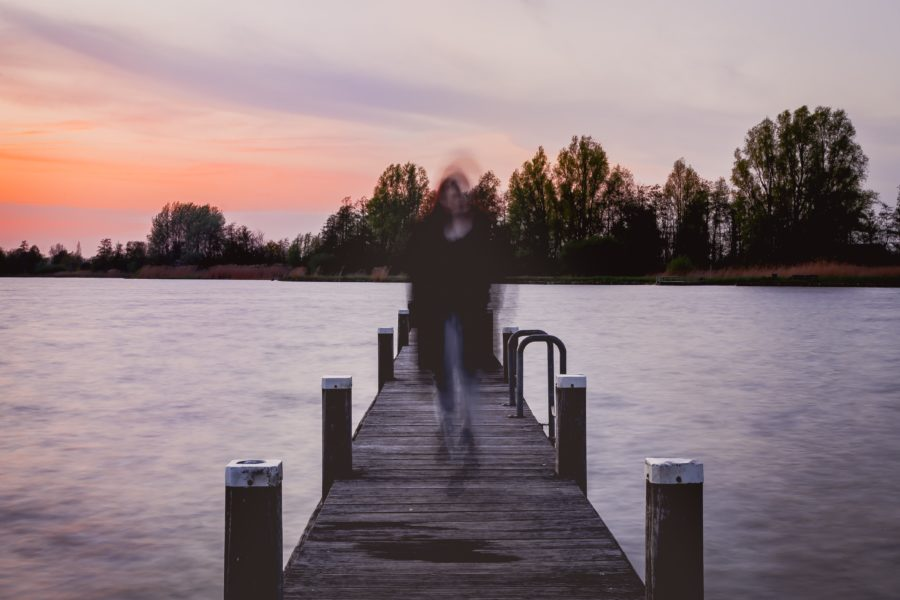 Blurry image of a woman standing on a pier at dusk