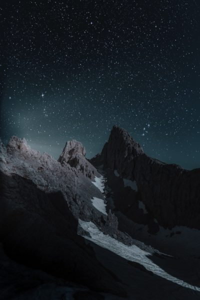 Night image of three peaks of mountains with a starry background