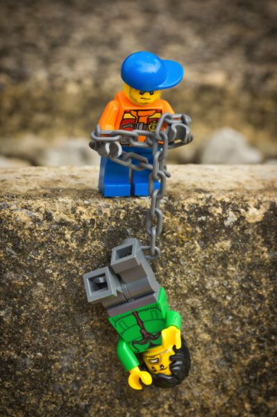 Image of a lego construction worker helping another lego worker