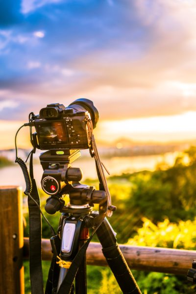 A black DSLR camera on a tripod taking images of a beautiful sunset using an intervalometer