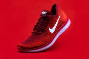 Red product display photograph of a Nike tennis shoe