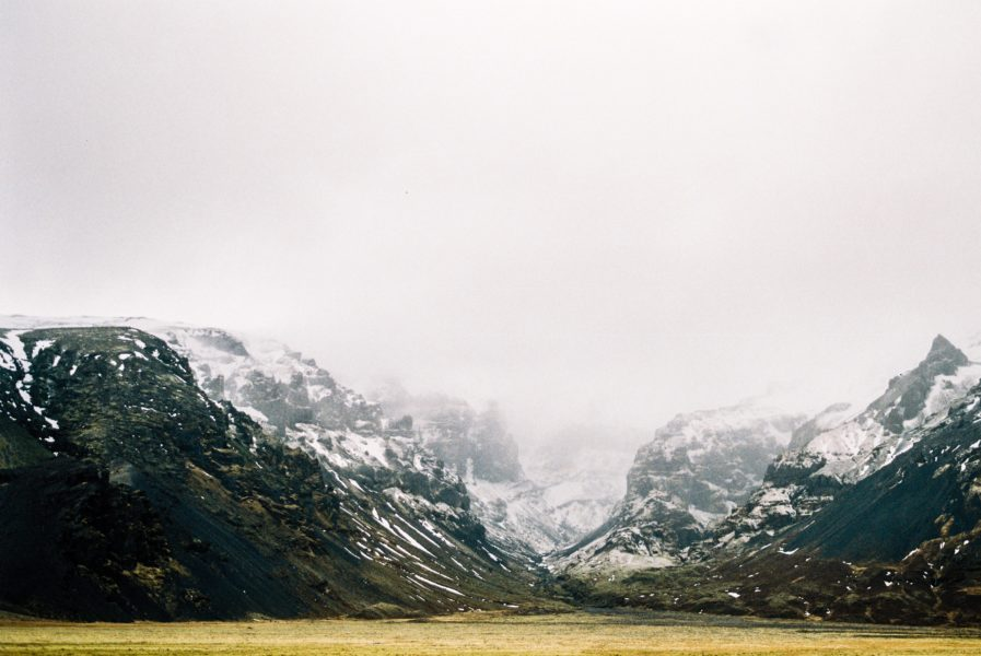 Scenic image of a mountain range with snow capped peaks behind white cloud and mist