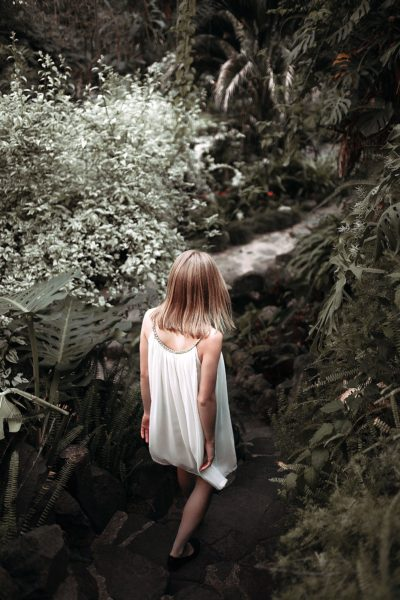 A girl wearing a white dress in a jungle
