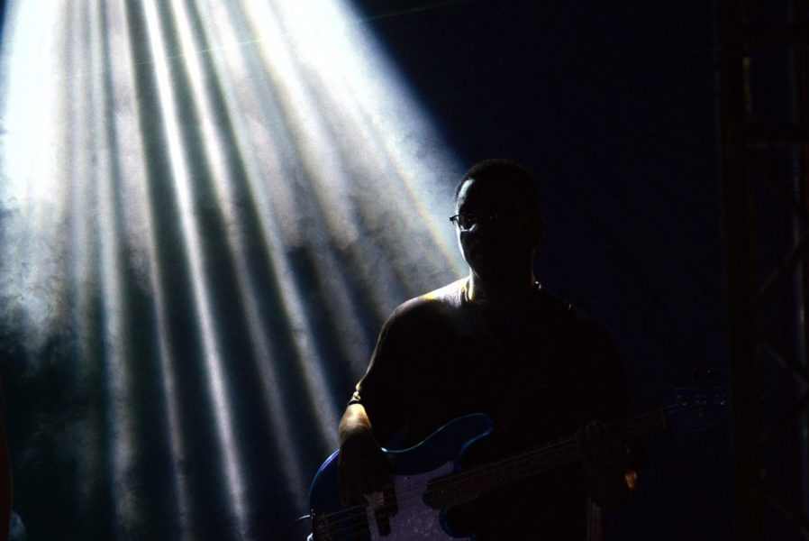 A musician playing the guitar in a lowly lit stage black and white image