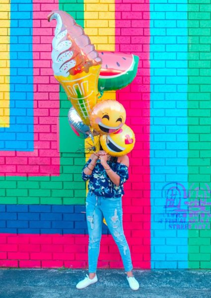 Young woman holding some balloons and standing in front of a brightly painted wall