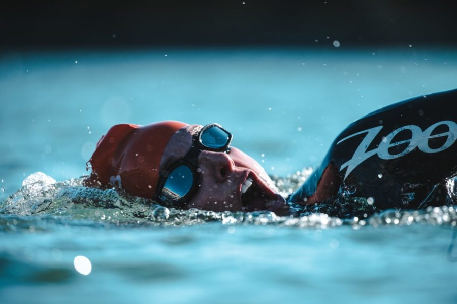 Man swimming in a natural lake for a race