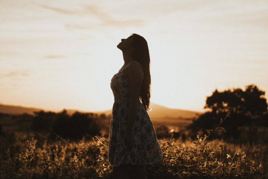Woman standing in a field on an evening. The photograph is backlit with the sun in the back