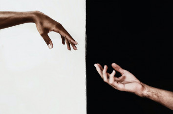 Two hands connecting over a black and white background