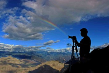 a photographer with a camera on a mountain top with clouds and a rainbow in the background