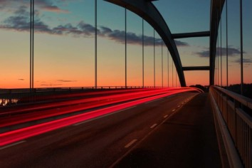 Long exposure image of a bridge with red and white light streaks of passing by cars