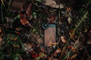 Mobile phone camera with external lens attached lying on a jungle floor
