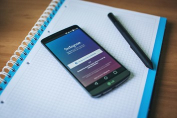 An android cell phone on a blue notebook with Instagram login page opened on it