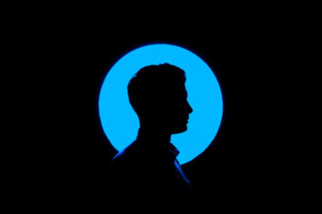 silhouette photography with a black background and a blue circle and a man standing in front of it.