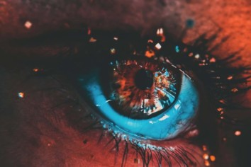 human eyes with a red and blue color light falling on it