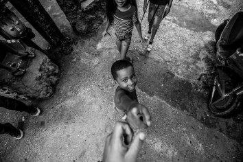 Street photograph of a young boy shaking hands with the photographer