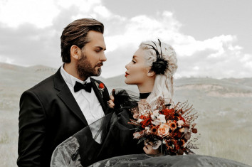 man-in-black-suit-holding-bouquet-of-flowers-panorama-portrait