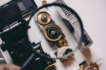 internal mechanics of a digital camera exposed with a magnification glass held above it