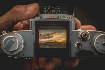 looking through the viewfinder of a film camera