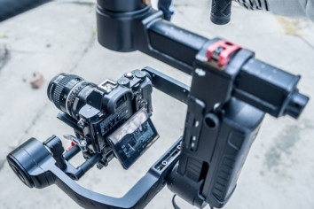A DSLR camera mounted on a gimbal with an attached microphone ready to shoot a video
